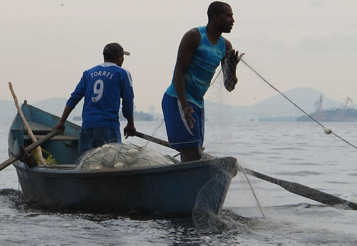 Jorge Cavalo, left, and Maicon Pele lay down a net for fishing in Mage, Brazil. Both work with Alexandre Anderson, who heads a fishermen's cooperative and is one of the few opponents of Brazil's rapidly expanding oil industry.