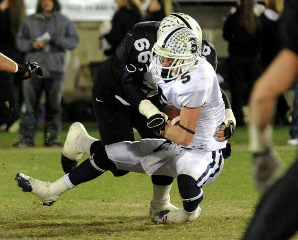 Staples' #5 Nick Kelly gets tackled by Xavier's #66 Henry Betar, during CIAC Class LL boys football championship action in East Hartford, Conn. on Saturday December 3, 2011. Photo: Christian Abraham / Connecticut Post