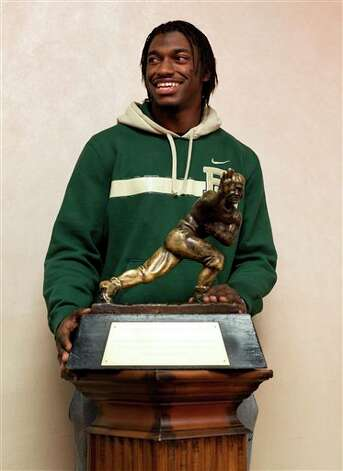 Baylor quarterback and Heisman Trophy finalist Robert Griffin III stands with the trophy after an informal roundtable conference with media members, Friday, Dec. 9, 2011, in New York. The winner will be announced in New York on Saturday. (AP Photo/John Minchillo) Photo: Associated Press