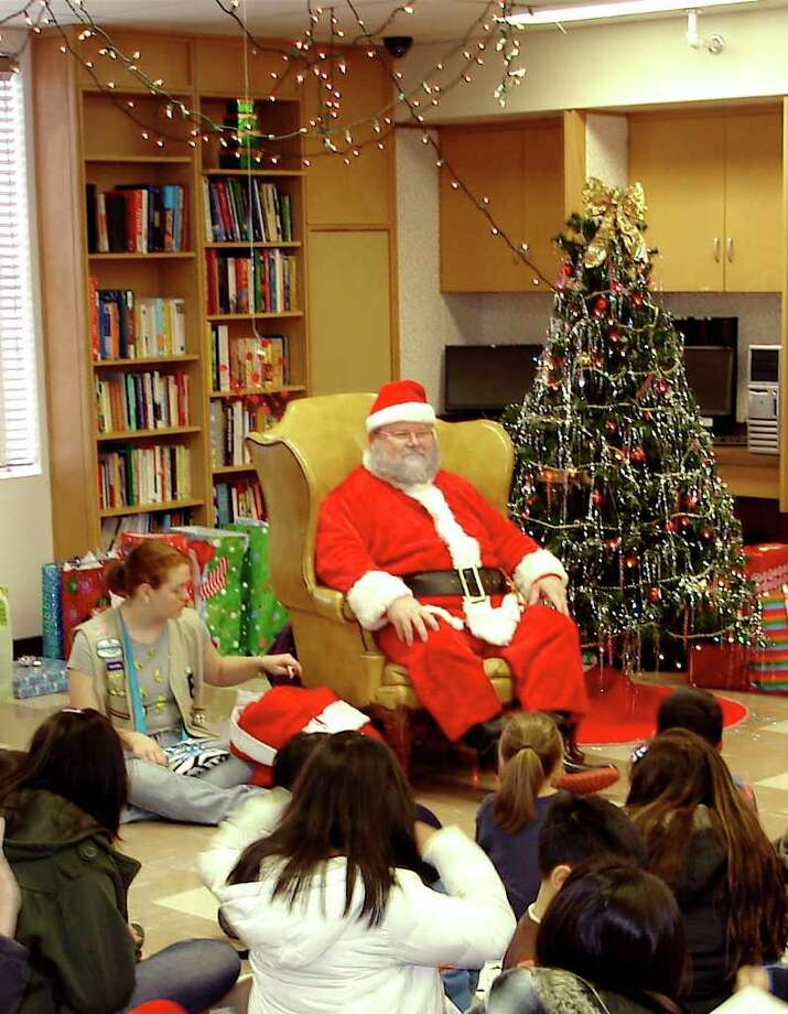 Several children sit at Santa's feet Saturday Dec. 10, 2011 as they await their names to be called to receive a present from jolly old St. Nick at The Summit, headquarters for Crosspoint Inc. Approximately 115 children gathered for the third annual Christmas celebration for kids of clients who are enrolled in Crosspoint's outpatient substance abuse and mental health programs. Photo: KEN SLAVIN / PHOTO COURTESY OF KEN SLAVIN