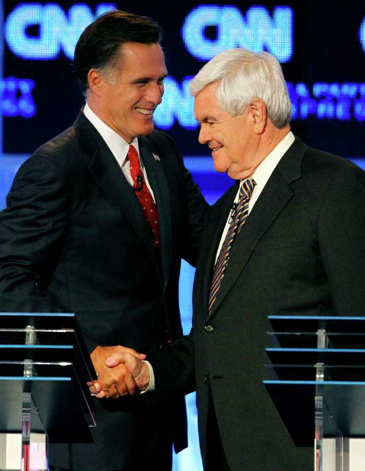 FILE - In this Sept. 12, 2011, file photo Republican presidential candidates former Massachusetts Gov. Mitt Romney, left, and former House speaker Newt Gingrich shake hands after a Republican presidential debate in Tampa, Fla. Gingrich is facing his first debate as the front-runner for the Republican presidential nomination Saturday night, Dec. 10, 2011. Standing next to him will be Romney, whose campaign has launched an all-out offensive against Gingrich's record and leadership style.  (AP Photo/Mike Carlson, File) Photo: Mike Carlson