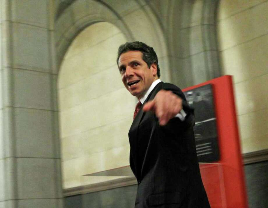New York Gov. Andrew Cuomo leaves the Capitol in Albany, N.Y., on Tuesday, Dec. 6, 2011. Cuomo and legislative leaders agreed to income tax cuts for New Yorkers making $40,000 to $300,000, which will save most middle-class families $300 to $400 a year. The tax cut of a fraction of 1 percentage point will be funded by an increase in the rate for taxpayers making more than $2 million a year. Those highest earners will pay an 8.2 percent rate, compared to the 6.85 percent rate they would have paid beginning Jan. 1 after a temporary surcharge expires on Dec. 31. (AP Photo/Mike Groll) Photo: Mike Groll