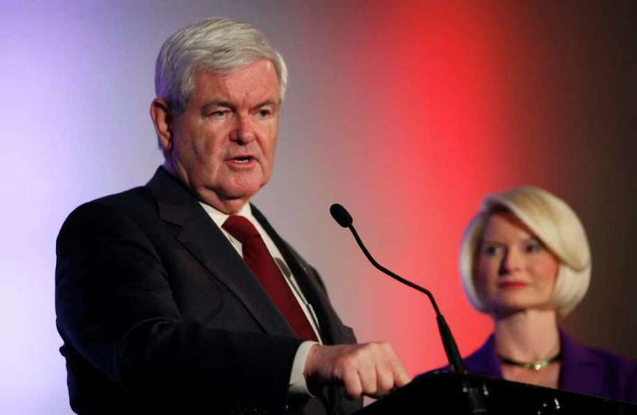 Republican presidential candidate and former House Speaker Newt Gingrich speaks during the Iowa Veterans Presidential Candidate Forum as his wife Callista looks on, Saturday, Dec. 10, 2011, in Des Moines, Iowa. (AP Photo/Charlie Neibergall) Photo: Charlie Neibergall