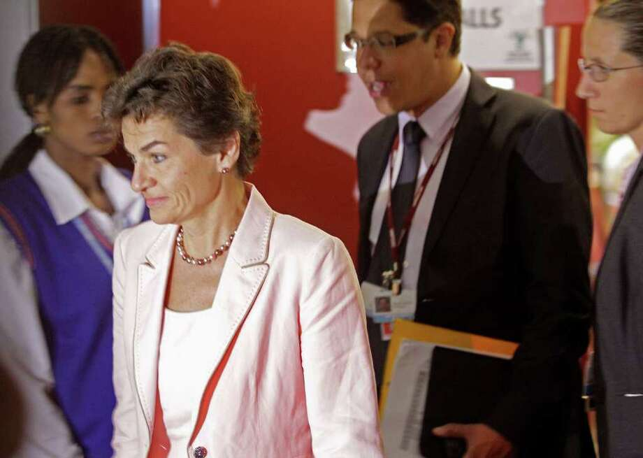 U.N. climate official Christiana Figueres walk out of  the negotiation room as the climate change summit nears it's end in the city of Durban, South Africa, Saturday, Dec 10, 2011. Some ministers and top climate negotiators left Durban without an agreement Saturday, with time running out and the prospect of an inconclusive end jeopardizing new momentum in the fight against global warming. (AP Photo/Schalk van Zuydam) Photo: Schalk Van Zuydam / AP