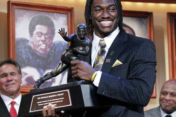 Robert Griffin III, of Baylor University, holds the Heisman Trophy award after being named the winner, Saturday, Dec. 10, 2011, in New York.