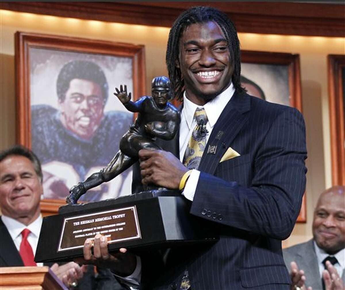 Robert Griffin III, of Baylor University, holds the Heisman Trophy award after being named the winner, Saturday, Dec. 10, 2011, in New York. (AP Photo/Kelly Kline)