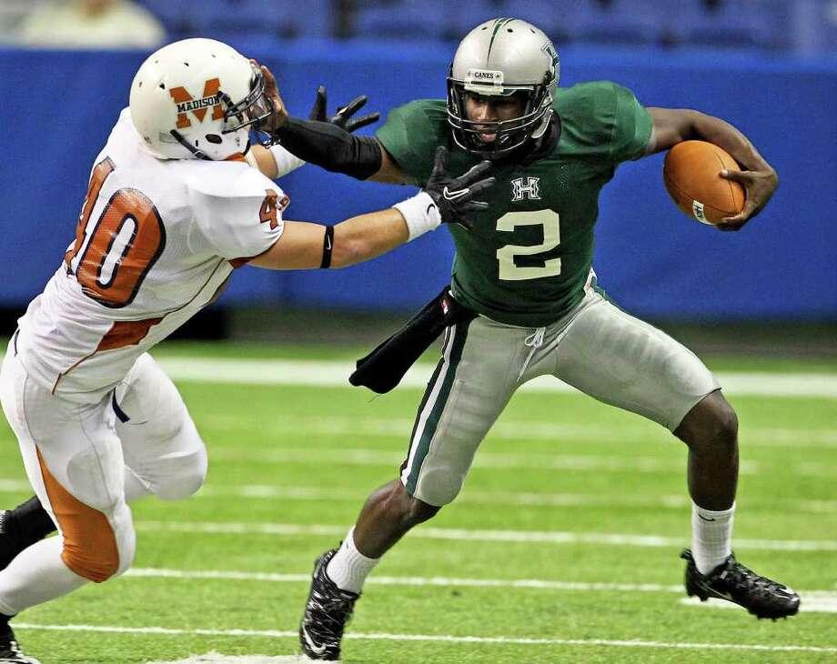 Hurricane quarterback Bralon Addison stiff arms Maverick defender Jesse Santos. Photo: TOM REEL, SAN ANTONIO EXPRESS-NEWS / © 2011 San Antonio Express-News