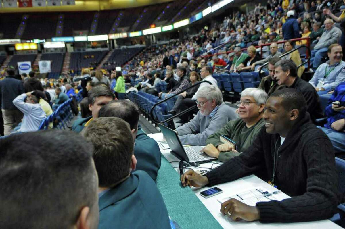 Former Siena basketball star Prosper Karangwa, right, now attends his alma mater's games as a scout for overseas leagues. He sits at his table with sports writers, before the start of the Siena-UAlbany game at the Times Union Center on Monday night Dec. 5, 2011 in Albany, NY. (Philip Kamrass / Times Union )