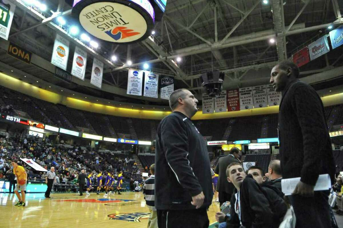 Former Siena basketball star Prosper Karangwa, right, now attends his alma mater's games as a scout for overseas leagues. He spoke with Albany Academy basketball coach Brian Fruscio, left, before the start of the Siena-UAlbany game at the Times Union Center on Monday night Dec. 5, 2011 in Albany, NY. (Philip Kamrass / Times Union )
