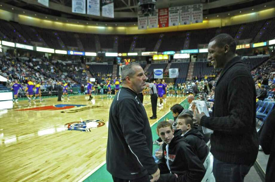 Former Siena basketball star Prosper Karangwa, right, now attends his alma mater's games as a scout for overseas leagues. He spoke with Albany Academy basketball coach Brian Fruscio, left, before the start of the Siena-UAlbany game at the Times Union Center on Monday night Dec. 5, 2011 in Albany, NY.  (Philip Kamrass / Times Union ) Photo: Philip Kamrass / 10015671A