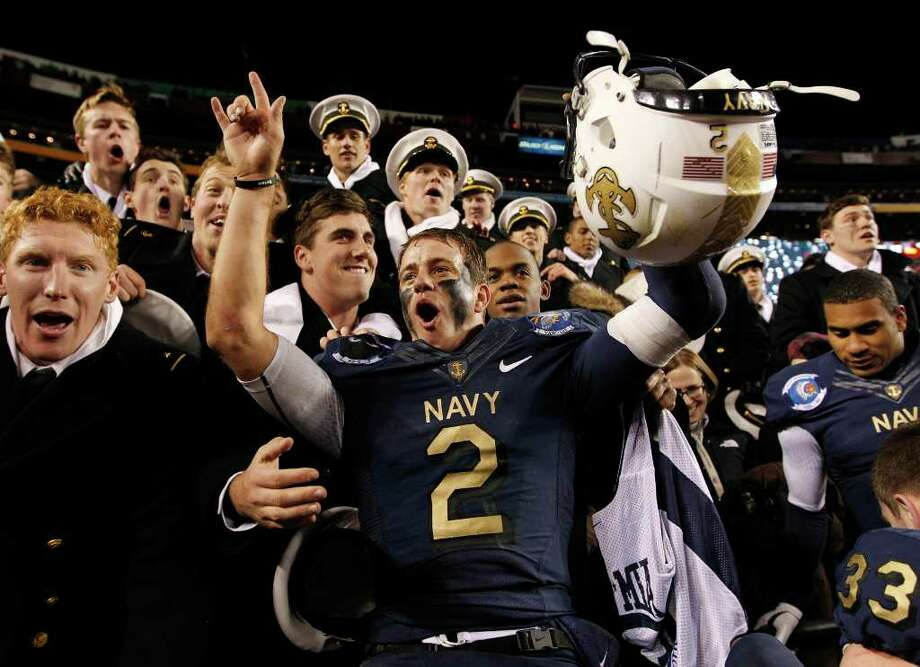 Navy quarterback Kriss Proctor, center, celebrates with Midshipmen after beating Army 27-21 in an NCAA college football game in Landover, Md., Saturday, Dec. 10, 2011. (AP Photo/Evan Vucci) Photo: Evan Vucci