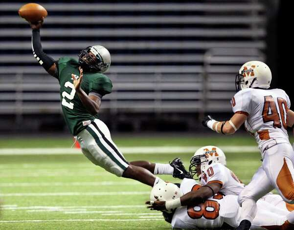Hurricane quarterback Bralon Addison finds a way to get rid of the ball while in the grasp of Maverick defenders in the first half as  Madison plays Fort Bend Hightower at the Alamodome in the state semifinal playoffs on December 10, 2011 Tom Reel/Staff Photo: TOM REEL, Express-News / © 2011 San Antonio Express-News