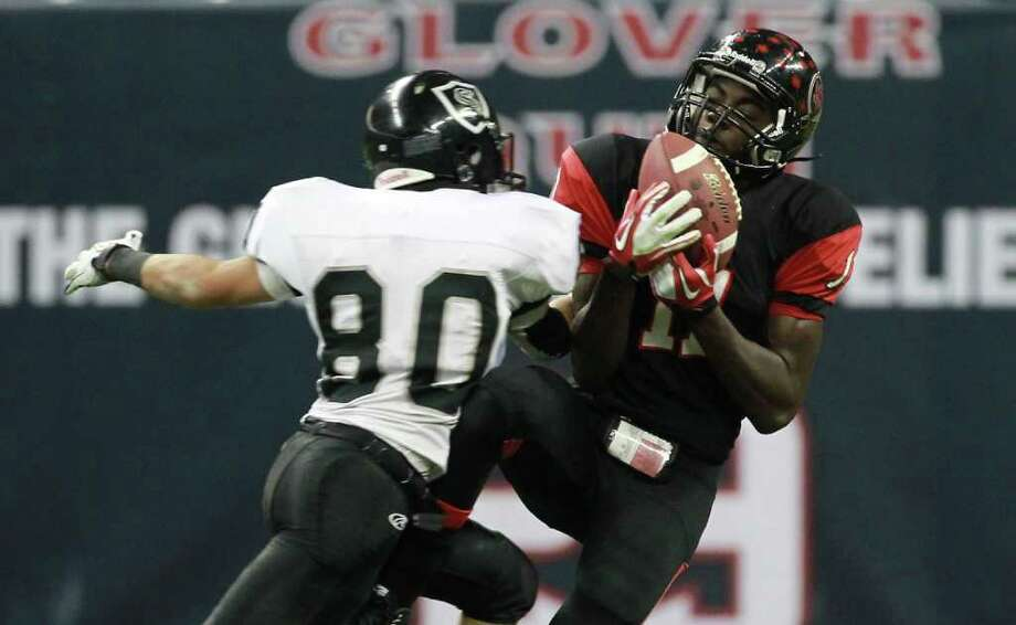 Port Arthur Memorial High School's Jhajuan Seales (11) pulls in the ball as Steele's Justin Garcia tries to defend during the fourth quarter of a Class 5-A Division II semifinal high school football game, Saturday, Dec. 10, 2011, in Reliant Stadium in Houston. Steele High won 51-31. Photo: Nick De La Torre, Houston Chronicle / © 2011  Houston Chronicle