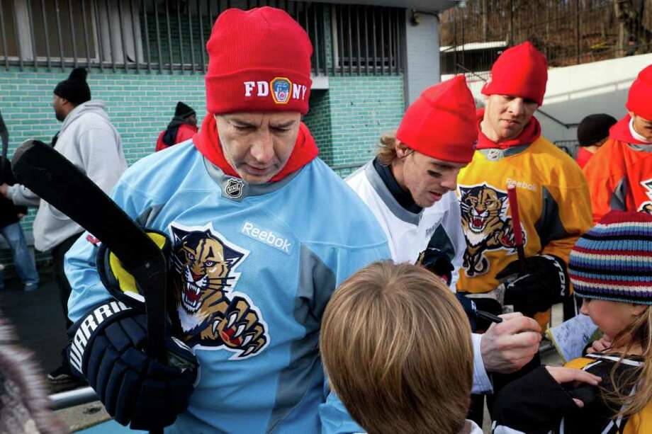 lorida Panthers head coach Kevin Dineen wears an FDNY hat as he signs autographs for fans after hockey practice at Central Park's Lasker Rink, Saturday, Dec. 10, 2011, in New York. The open-air rink has begun attracting visiting teams for short practices. (AP Photo/John Minchillo) Photo: John Minchillo