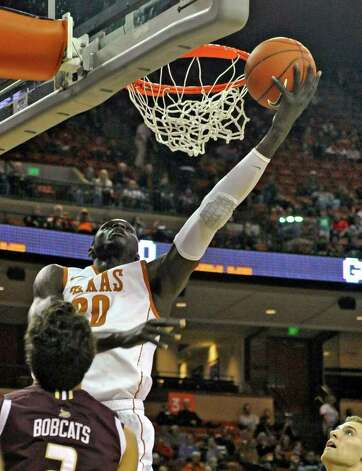 Texas forward Alexis Wangmene, rear, lays the ball up against Texas State forward Brooks Ybarra, front, during the first half of an NCAA college basketball game Saturday, Dec. 10, 2011, in Austin, Texas. Photo: AP
