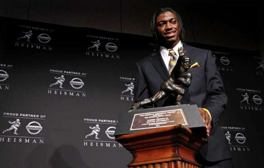 Heisman Trophy winner Robert Griffin III, of Baylor, is photographed with the award during a news co
