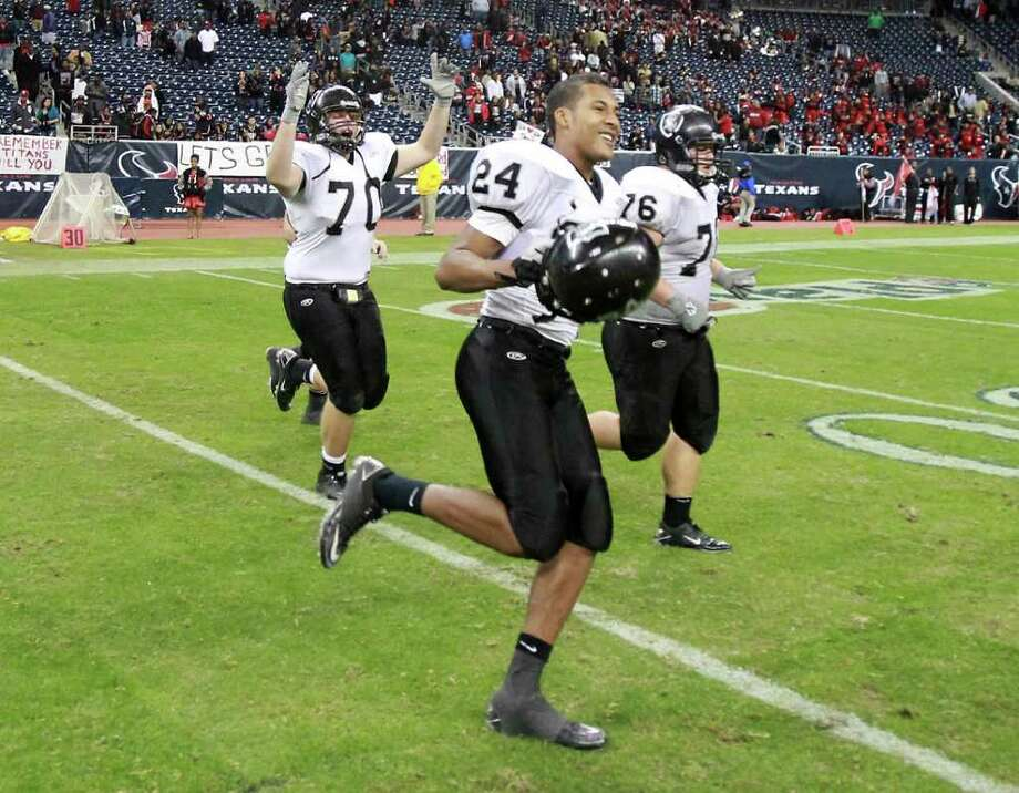 Cibolo Steele High School players Josh Obuch (70) Jaylen Harris (24), and Stephen Copenhaver, run to their band after shaking hands with Port Arthur Memorial High School and winning a Class 5-A Division II semifinal high school football game, Saturday, Dec. 10, 2011, in Reliant Stadium in Houston. Steele High won 51-31. Photo: Nick De La Torre, Houston Chronicle / © 2011  Houston Chronicle