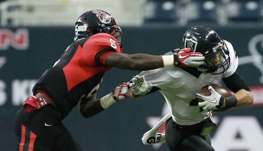 Port Arthur High School's Joshua Pickett, left, is flagged for grabbing Cibolo Steele High School's Justin Stockton's face mask during the first quarter of a Class 5-A Division II semifinal high school football game, Saturday, Dec. 10, 2011, in Reliant Stadium in Houston. Photo: Nick De La Torre, Houston Chronicle / © 2011  Houston Chronicle