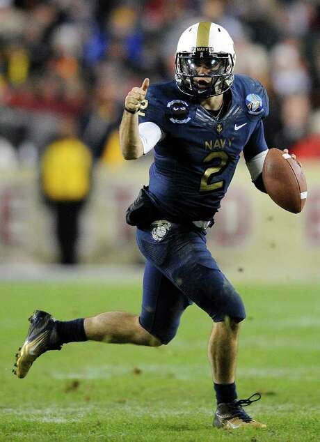 NICK WASS : AP ON THE RUN: Navy quarterback Kriss Proctor directs traffic in the second half of the win over Army. Photo: Nick Wass / FR67404 AP