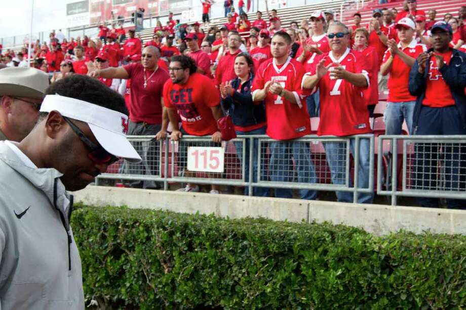 Smiley N. Pool : Chronicle ON HIS WAY OUT: Fans cheer UH head coach Kevin Sumlin, left, after his final game with the Cougars, a 49-28 loss to Southern Miss in the C-USA title game. Photo: Smiley N. Pool / © 2011  Houston Chronicle