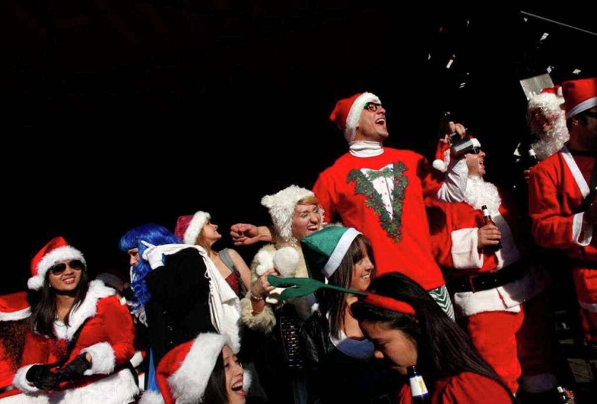 NEW YORK, NY - DECEMBER 10: Revelers dressed as Santa Claus drink outside at a bar during the annual SantaCon event December 10, 2011 in New York City. SantaCon is a mass gathering of revelers dressed as Santa Claus who take to the streets in cities across the country before Christmas. (Photo by Allison Joyce/Getty Images)