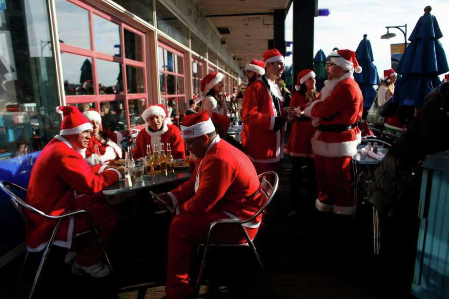 NEW YORK, NY - DECEMBER 10:  Revelers dressed as Santa Claus drink outside at a bar during the annual SantaCon event December 10, 2011 in New York City. SantaCon is a mass gathering of revelers dressed as Santa Claus who take to the streets in cities across the country before Christmas. (Photo by Allison Joyce/Getty Images) Photo: Allison Joyce, Getty Images / 2011 Getty Images