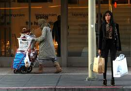 A woman pushes her belonging up Mission Street in front of Bloomingdales department store. San Francisco is a tale of two cities: people down and out on their luck people coexisting with the good life, right next door Thursday December 8, 2011