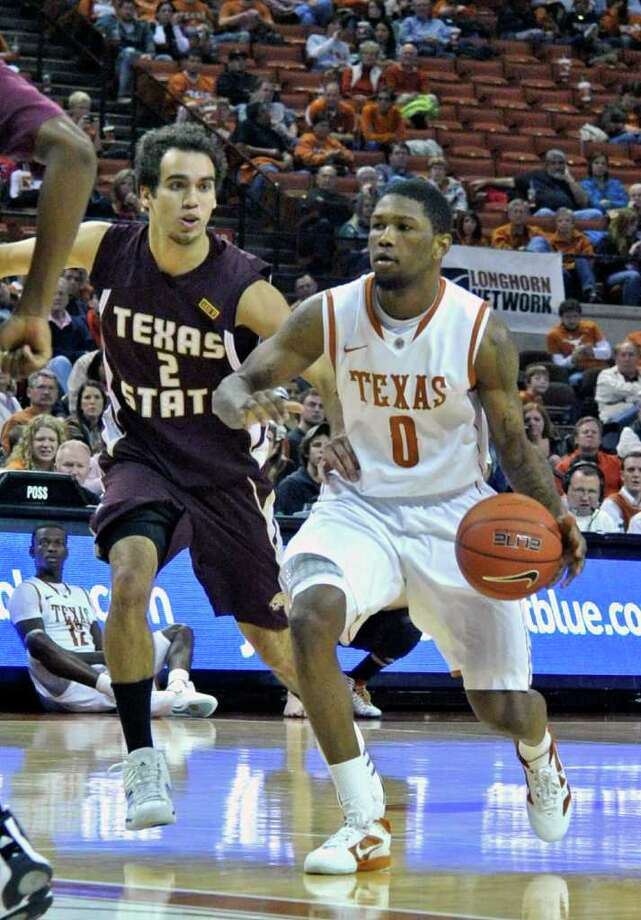 Texas guard Julien Lewis, right, goes to the lane against Texas State guard Brooks Ybarra during the second half of an NCAA college basketball game, Saturday, Dec. 10, 2011, in Austin, Texas. Lewis led all scorers with 19 points. Texas won 86-52. (AP Photo/Michael Thomas) Photo: Michael Thomas, Associated Press / FR65778 AP