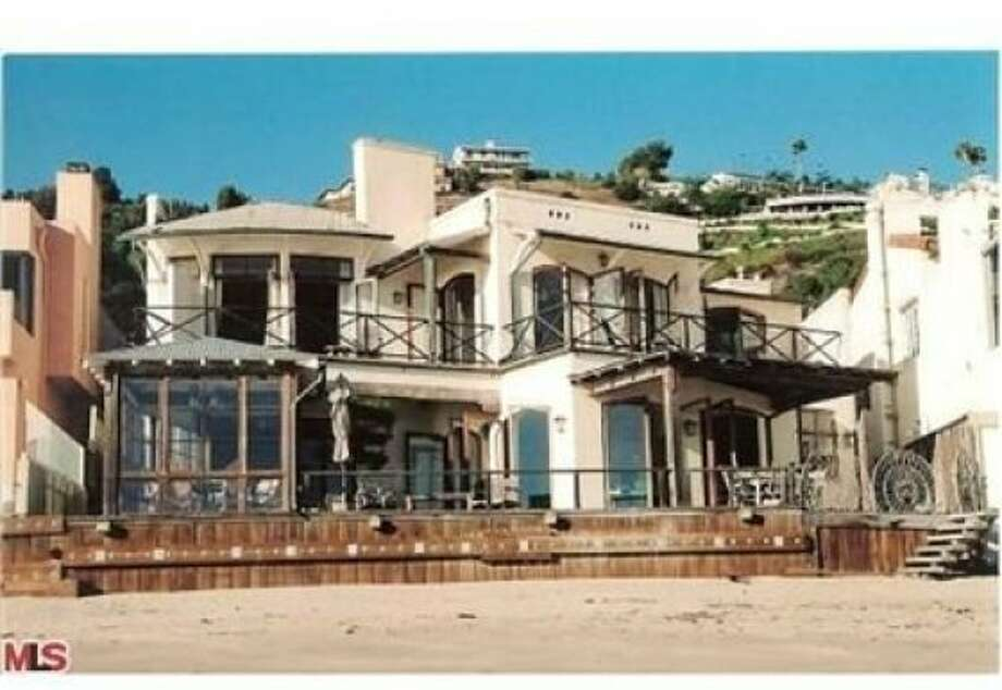 An exterior view of the beachfront side of the home, revealing that it's just a quick stroll through the sand from the ocean to the patio. Photo: Realtor.com, Coldwell Banker