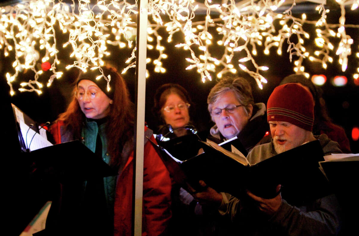 The Seattle Bach Choir sings Christmas carols at the Green Lake Pathway of Light celebration along the Green Lake Trail in Seattle on Saturday, Dec. 10, 2011. Thousands gather to walk around the lake and listen to holiday performances. Many people wear holiday lights or adorn their dogs in them and walk around the lake. This event has been held in Seattle for the past 35 years.