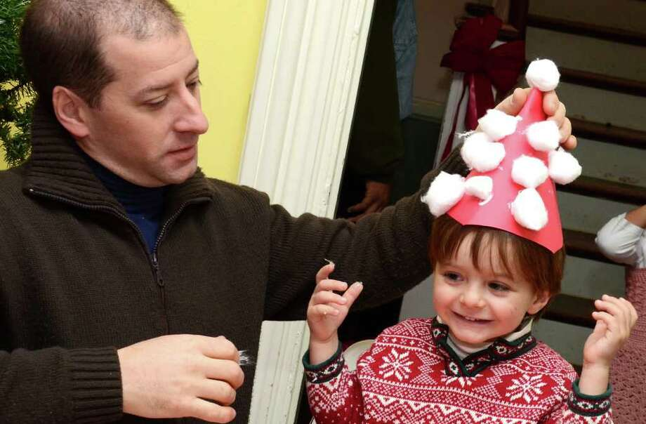 Arthur Zarra, 3, grins as his father, Robert Zarra, of Fairfield, places a construction paper santa hat on his head during the Visit to Santa's House event at the Burr Homestead sponsored by the Junior Women's Club of Fairfield on Sunday, Dec. 11, 2011. Photo: Amy Mortensen / Connecticut Post Freelance