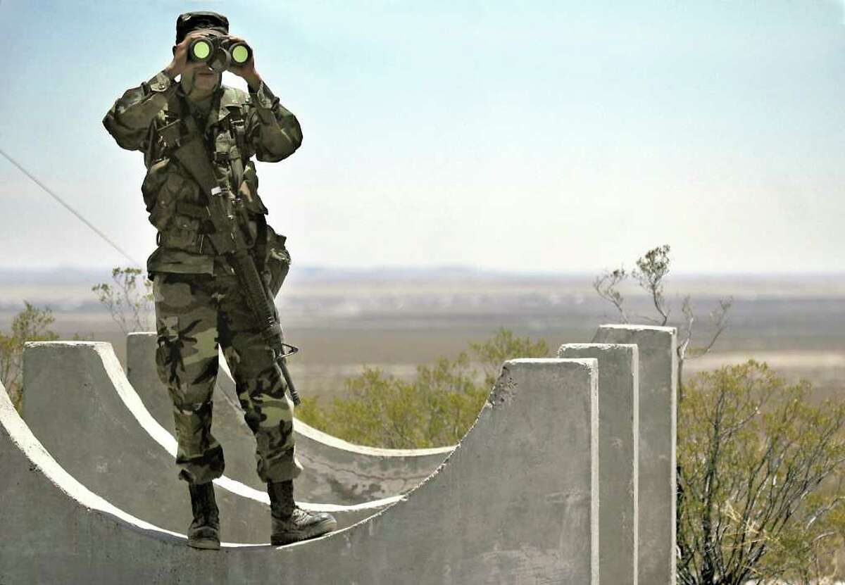 Army National Guard Spc. Gustavo Gutierrez, 23, of Las Cruces, N.M., scans the U.S./Mexico border Monday, June 12, 2006, from the top of Radar Hill, near Columbus, N.M. He is part of Operation Jump Start, which has the National Guard deploying troops to patrol the border in an effort to curb illegal immigrants from entering the country. (AP Photo/Las Cruces Sun-News, Norm Dettlaff)