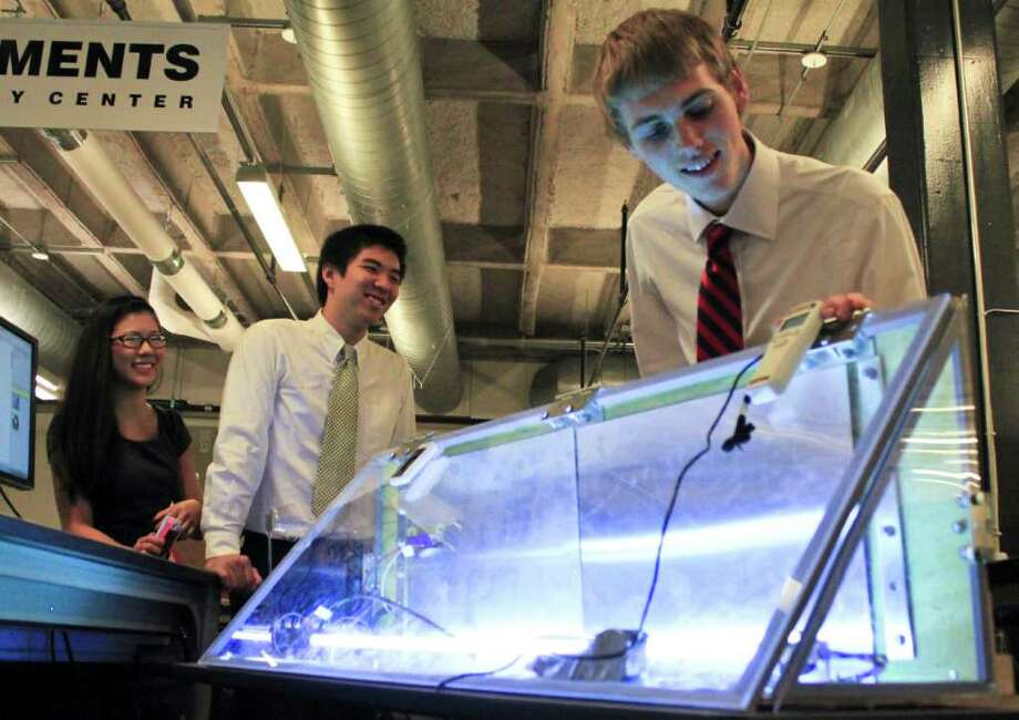 Rice University bioengineering students Grace Ching (from left), Shidong Chen and Joey Spinella demonstrate a device they built and designed to help minimize germs, specifically Tuberculosis, on Metro buses Tuesday, Dec. 6, 2011, in Houston.  (Hallie Jordan / Houston Chronicle) Photo: Hallie Jordan / © 2011 Houston Chronicle