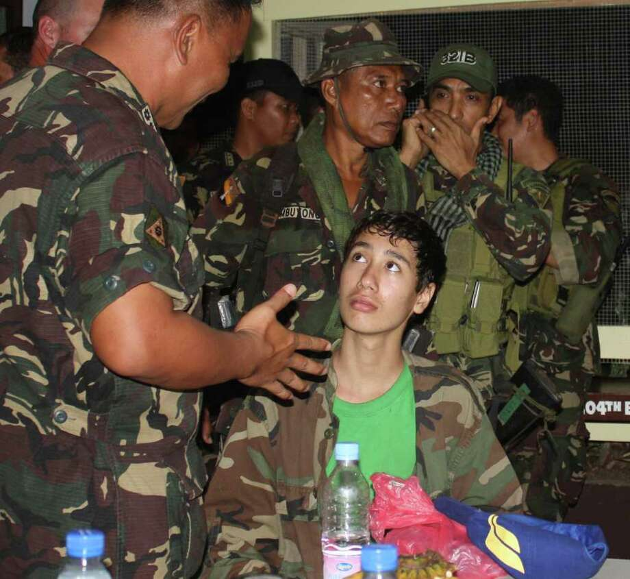 ASSOCIATED PRESS SAFE:  Kevin Lunsman, talks to soldiers in Zamboanga city, Philippines. The boy had been held five months by  al-Qaida-linked militants. / AP