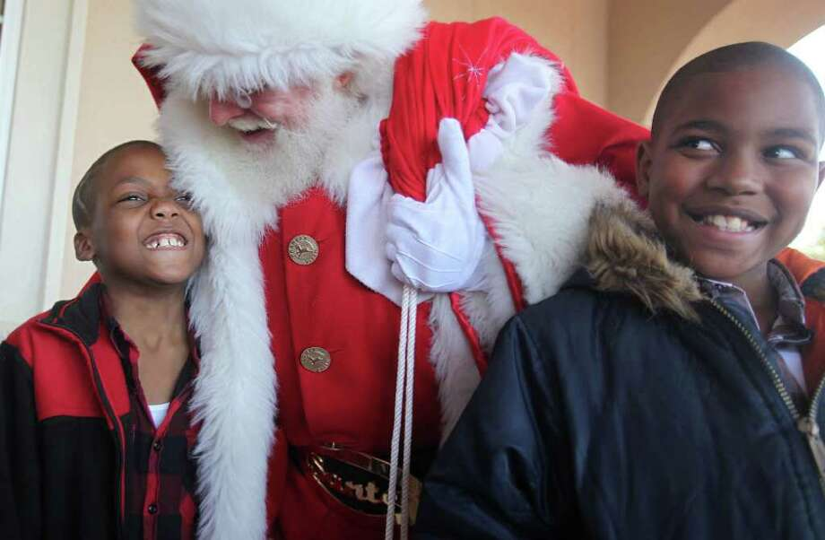 "Cancer patient Jayshawn Dixon, 8, and brother Marcus Evans, 9, greet Santa Claus during the ""Stuff the Sleigh"" holiday party at the Firethorne Visitor Center Sunday, Dec. 11, 2011, in Katy. Approximately 19 children with cancer, 51 siblings and parents from the Texas Children's Hospital West Campus receive Christmas gifts. Photo: Mayra Beltran, Houston Chronicle / © 2011 Houston Chronicle"