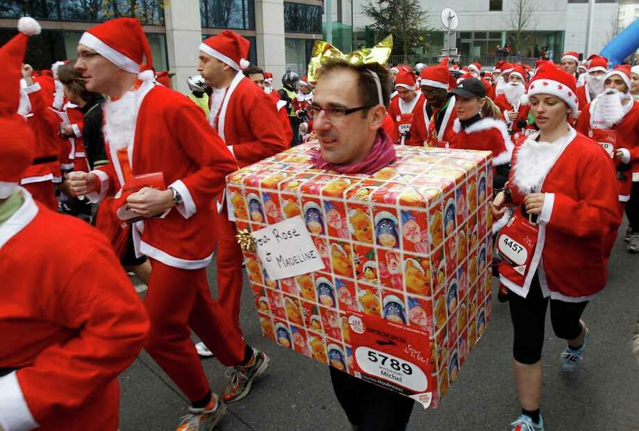 "Runners, dressed as Santa Claus take part to the traditional ""Christmas Corrida Race"" in the streets of Issy Les Moulineaux, on the western outskirts of Paris, Sunday, Dec. 11, 2011. Photo: REMY DE LA MAUVINIERE, Associated Press / AP"
