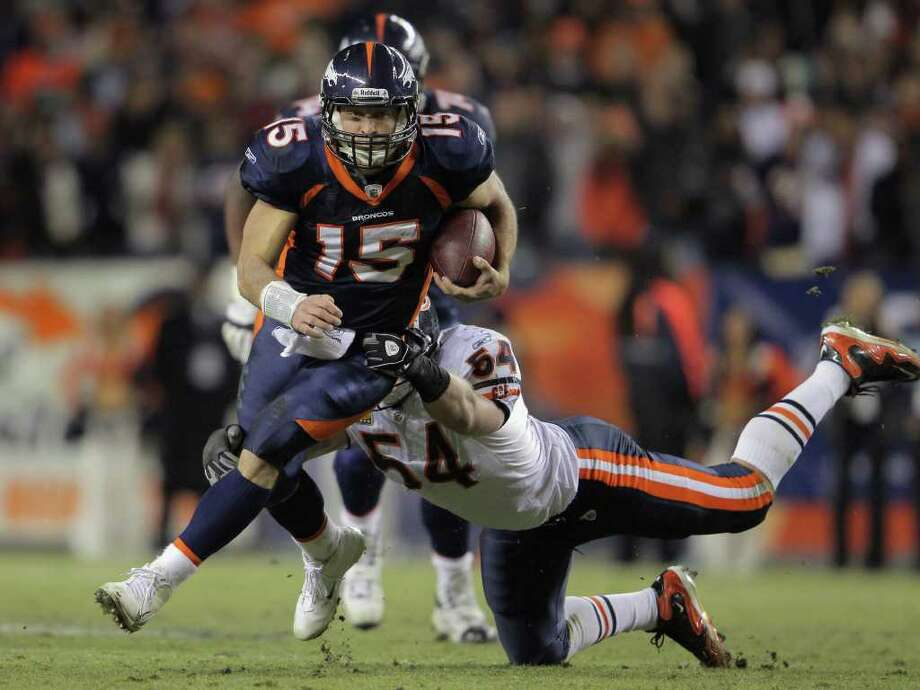 DOUG PENSINGER: GETTY IMAGES SCRAMBLING TOWARD VICTORY: Quarterback Tim Tebow shakes off a tackler as he picks up yardage during Denver's drive to a game-winning field goal in overtime. Photo: Doug Pensinger / 2011 Getty Images