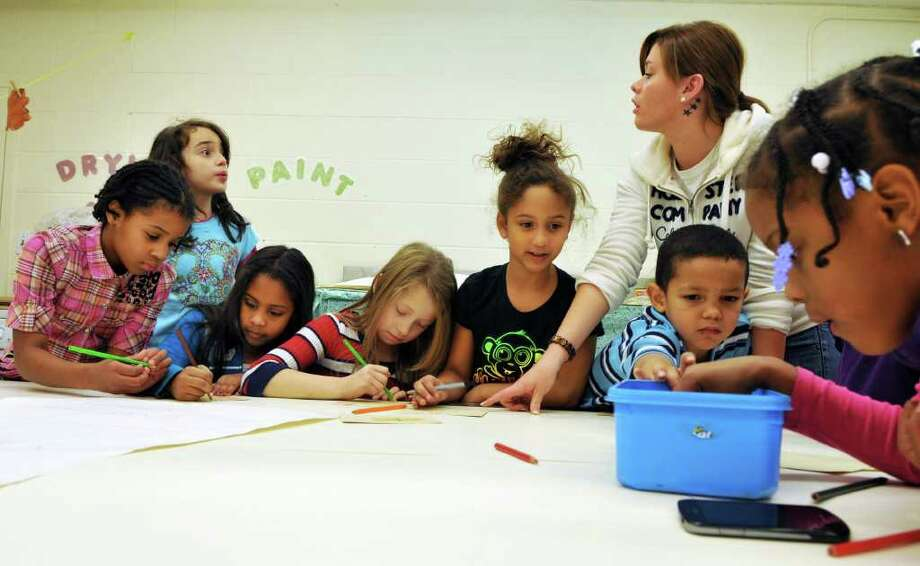 Counsellor Tiffany Bushey, top, helps kids make Christmas cards in the arts and crafts room at the Lansingburgh Boys & Girls Club Friday Dec.9, 2011.  (John Carl D'Annibale / Times Union) Photo: John Carl D'Annibale / 10015688A