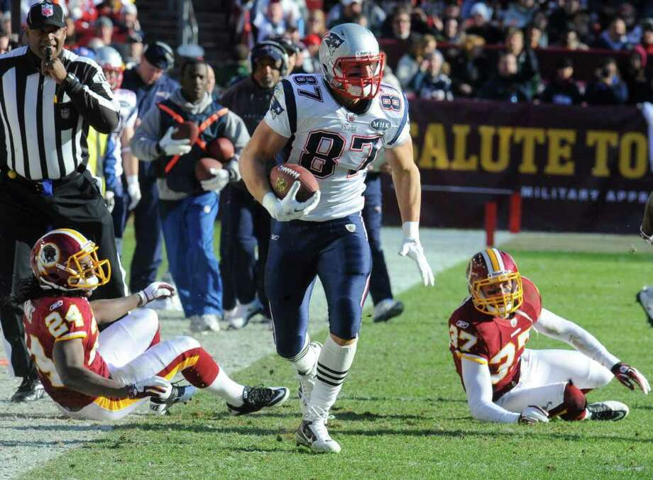 New England Patriots tight end Rob Gronkowski (87) runs past Washington Redskins strong safety DeJon Gomes (24) and Washington Redskins free safety Reed Doughty (37) during the first half of an NFL football game on Sunday, Dec. 11, 2011, in Landover, Md.  (AP Photo/Rich Lipski) Photo: Rich Lipski