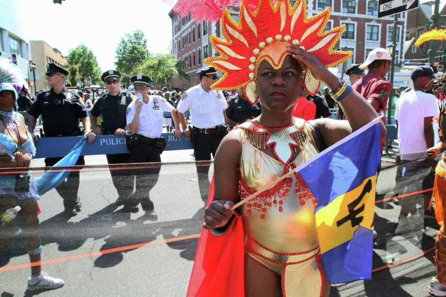 """In this Sept. 26, 2010 photo, police stand along the route of the West Indian-American Day Parade as parade participants make their way along Eastern Parkway in the Brooklyn borough of New York. The New York Police Department is investigating a Facebook group purported to be created by police officers entitled """"No More West Indian Day Detail,"""" rife with nasty, often racist comments about the annual parade in Brooklyn that has been marred by violence, including this year when two people were fatally shot. (AP Photo/Tina Fineberg) Photo: Tina Fineberg"""