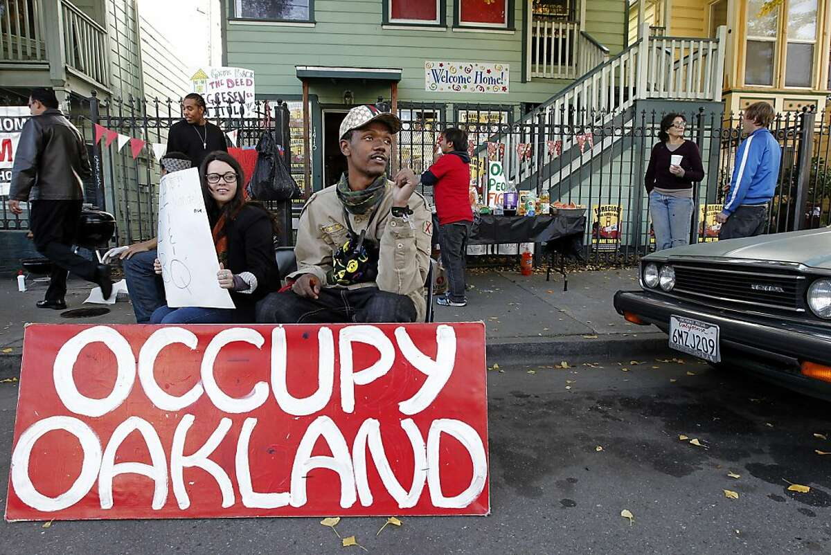 Gricelda Gutierrez and Melvin Kelley inform passersby of the free barbeque, as members of Occupy Oakland continue their occupation of a vacant home at 1415-1417 10th Street, on Friday December 10, 2011, in Oakland, Ca. Two foreclosed properties in West Oakland properties have been taken over and occupied, one bi it's former owner Gayla Newsome and the other by members of Occupy Oakland.