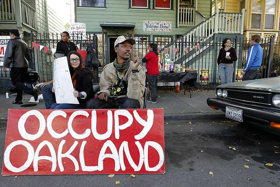 Gricelda Gutierrez and Melvin Kelley inform passersby of the free barbeque, as members of Occupy Oakland continue their occupation of a vacant home at 1415-1417 10th Street, on Friday December 10, 2011, in  Oakland, Ca. Two foreclosed properties in West Oakland properties have been taken over and occupied, one bi it's former owner Gayla Newsome and the other by members of Occupy Oakland. Photo: Michael Macor, The Chronicle