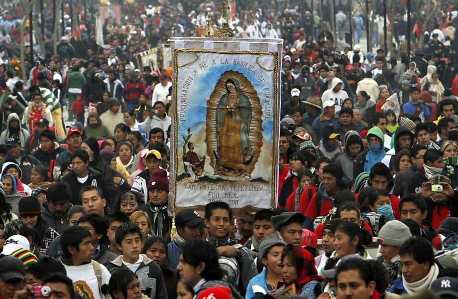 Pilgrims carry an image of Our Lady of Guadalupe toward the Basilica of the Virgin of Guadalupe in Mexico City, Sunday Dec. 11, 2011. Hundreds of thousands of Mexicans are making the pilgrimage to the shrine in anticipation of the Catholic icon's feast day on Dec. 12.  Also known as La Morenita, Our Lady of Guadalupe is Mexico's most popular religious and cultural image. (AP Photo/Marco Ugarte) Photo: Marco Ugarte, AP