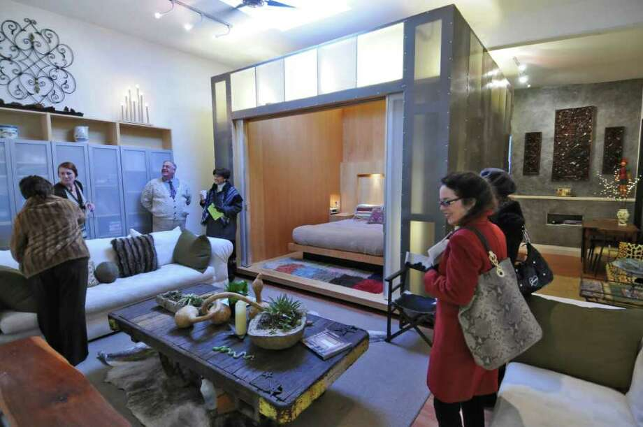 Visitors inspect the Z Box, a prototype bedroom on wheels, designed by Dan Hisel and homeowner Will Vosecek, inside of 328 Ontario Street, a loft that was converted from a former plumber's warehouse, during the Historic Albany Foundation's 9th annual Holiday House Tour 2011 on Sunday Dec. 11, 2011 in Albany, N.Y.  This loft is for sale for $165, 000. (Philip Kamrass / Times Union ) Photo: Philip Kamrass / 00015476A