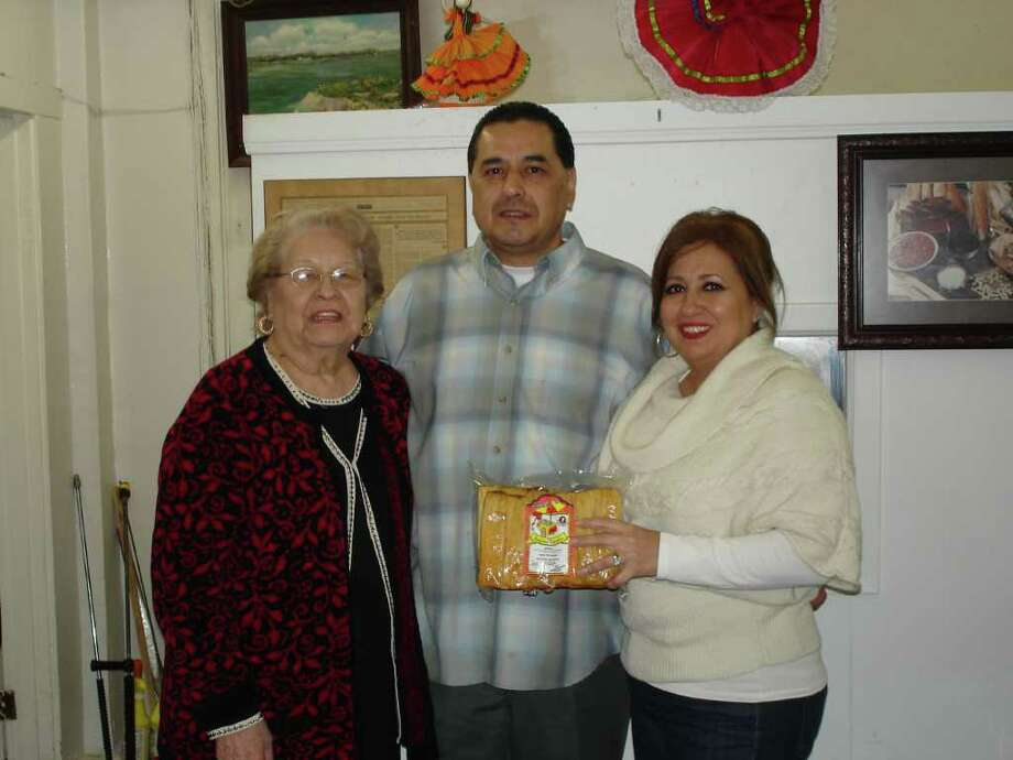 Josephine DeLeon poses with her son Gene and his wife Dahlia (right) with their famous handmade Rudy's Tamales.