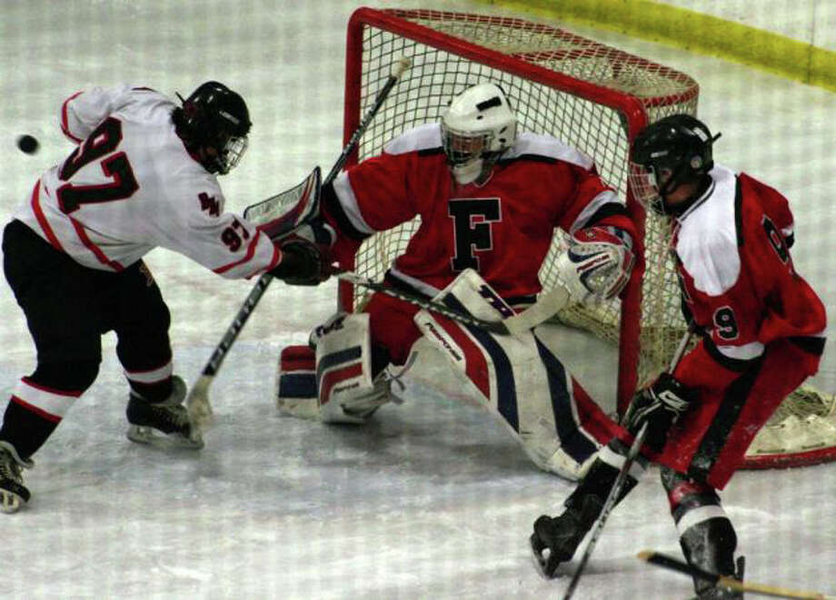Fairfield goalie Connor Frawley, stopping a shot in action against Branford last year, will serve as the co-op hockey team's goalie again this year. Photo: File Photo