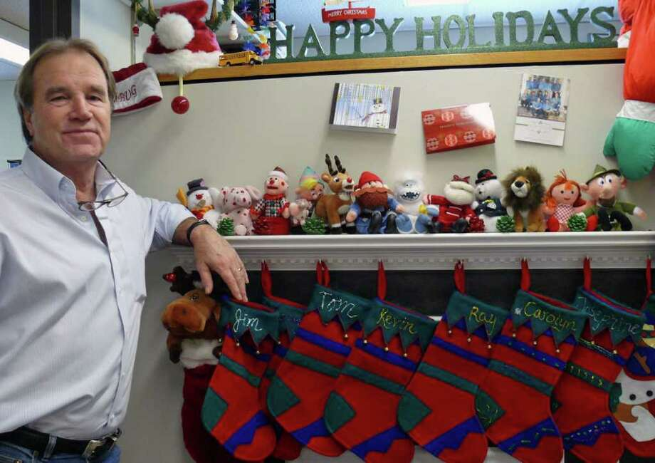 """Building Official James Gilleran poses by the """"fireplace"""" in the Buiding Department. The department is all decked out for the holidays. Photo: Genevieve Reilly / Fairfield Citizen"""