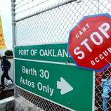 A protesters passes a sign for the Port of Oakland on Monday, Dec. 12, 2011, in Oakland, Calif.