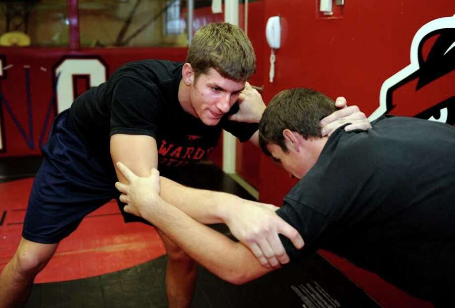 Fairfield Warde senior James Heinzman grapples with coach Brandon McBreairty Wednesday, Dec. 7, 2011 during wrestling practice at the school. Photo: Autumn Driscoll / Connecticut Post