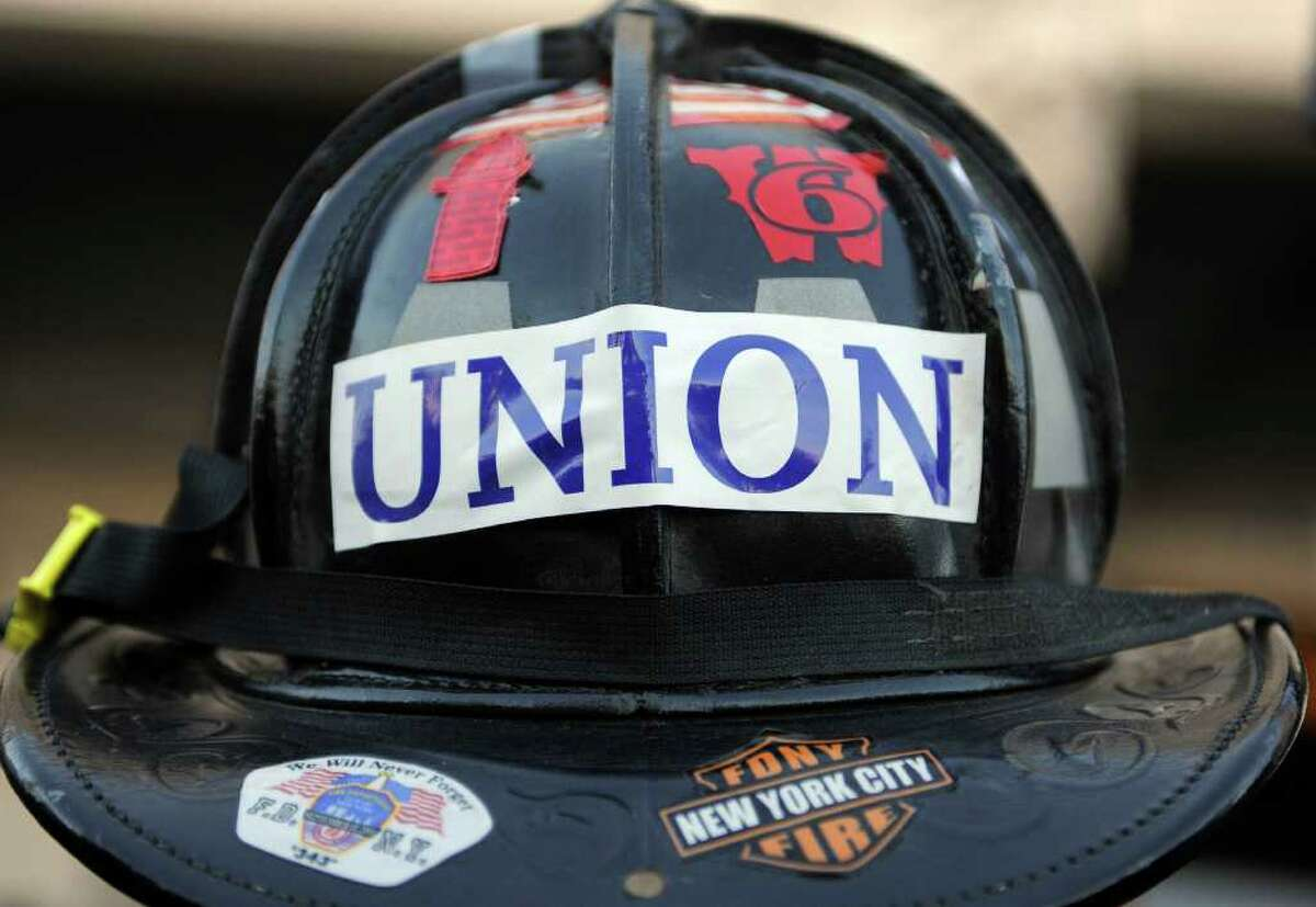 Mike Osiecki of South Fire District IAFF Local 3918, of Middletown, wears his fire helmet during a rally of union workers in support of unionized public employees in Wisconsin, at the Capitol in Hartford, Conn., Wednesday, Feb. 23, 2011. Dan Malloy addressed the crowd even as his administration plunged toward a fight over pay and pensions.